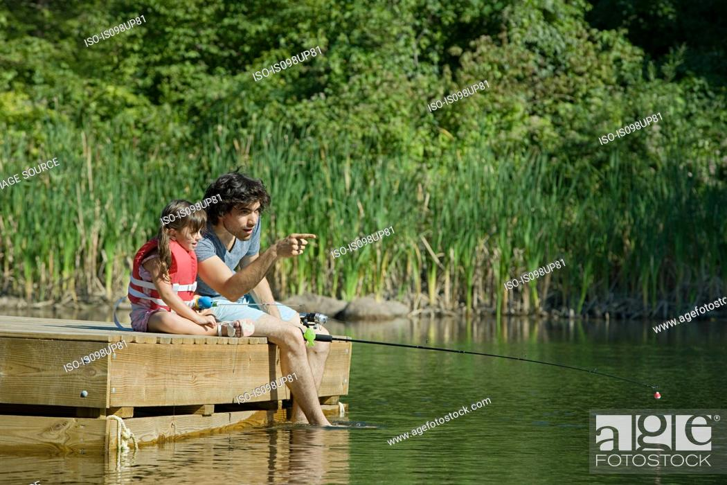Stock Photo: Father and daughter fishing from jetty.