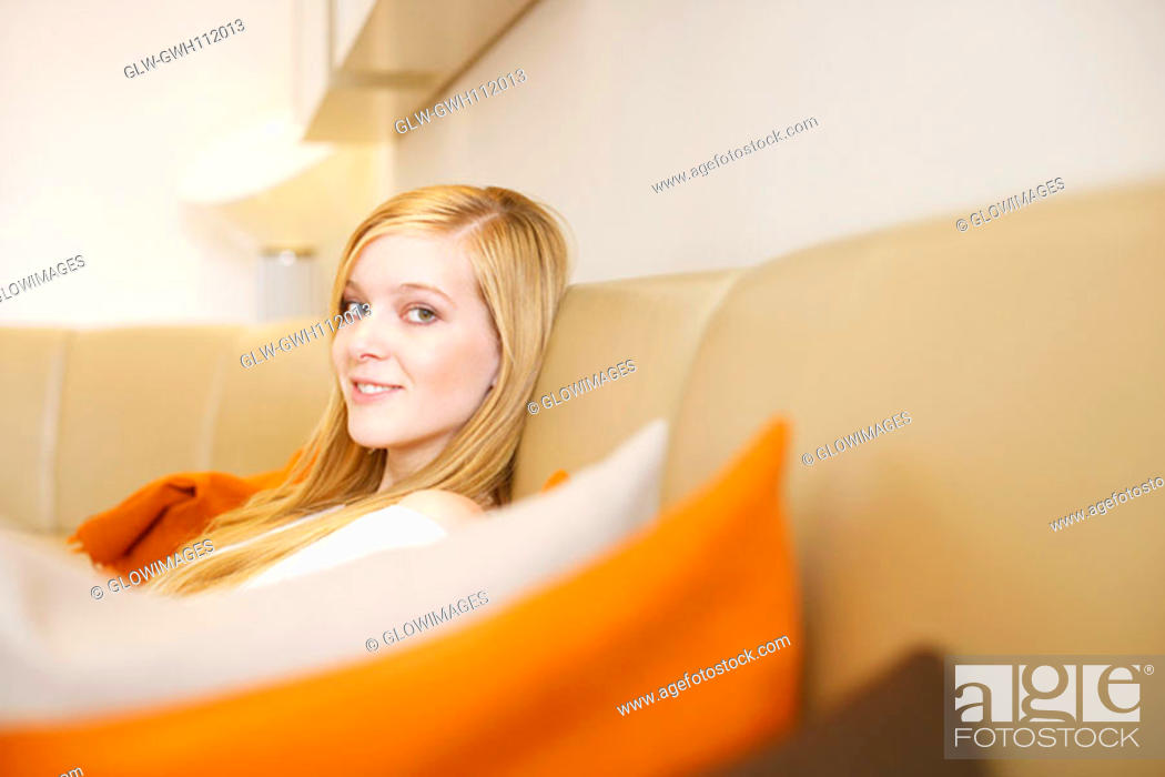 Stock Photo: Portrait of a young woman sitting on a couch.