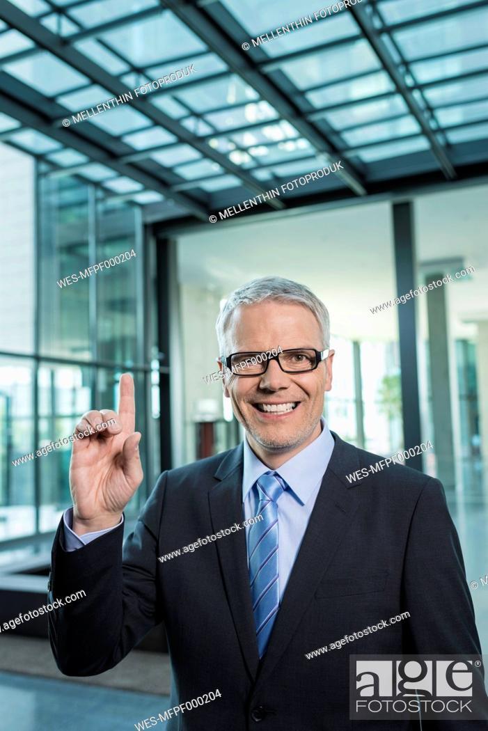 Stock Photo: Germany, Stuttgart, Businessman with one finger, smiling, portrait.