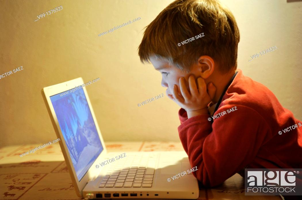 Stock Photo: young boy who watches a movie on the computer.