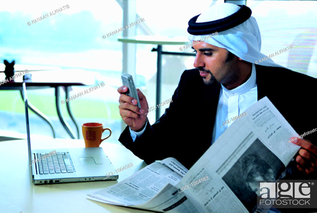 Stock Photo: Arab businessman checking his mobile phone in the office.