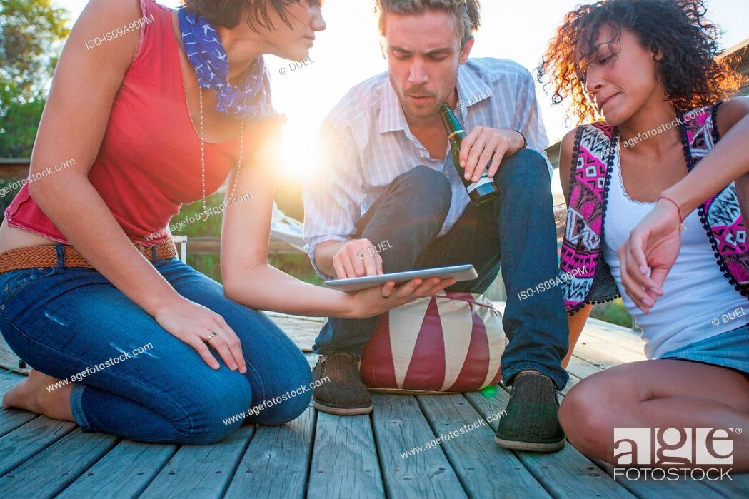 Stock Photo: Young women and man using digital tablet on decking.
