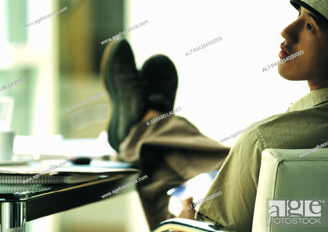 Stock Photo: Man sitting in chair with feet on table, looking to the side, rear view.