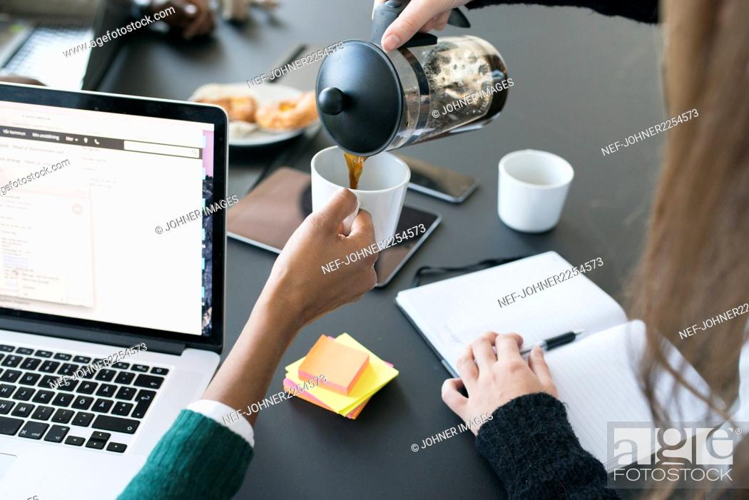 Stock Photo: Women pouring coffee into coffee cup in office.