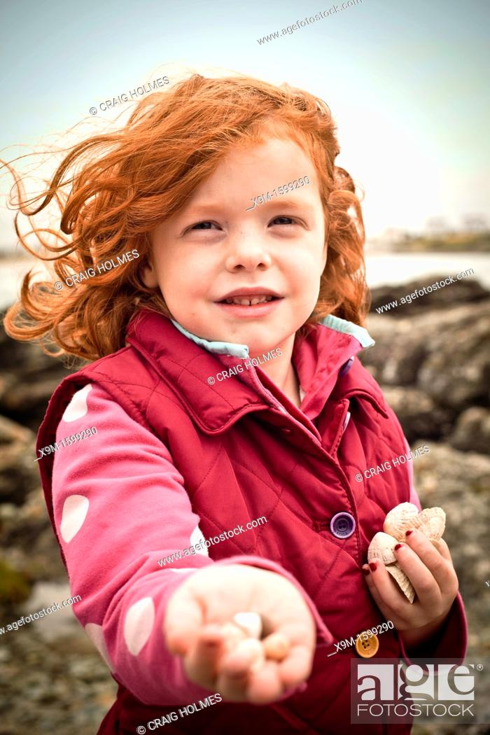 Stock Photo: A little girl, aged 5, holding a sea shells on a beach, on a cold day.