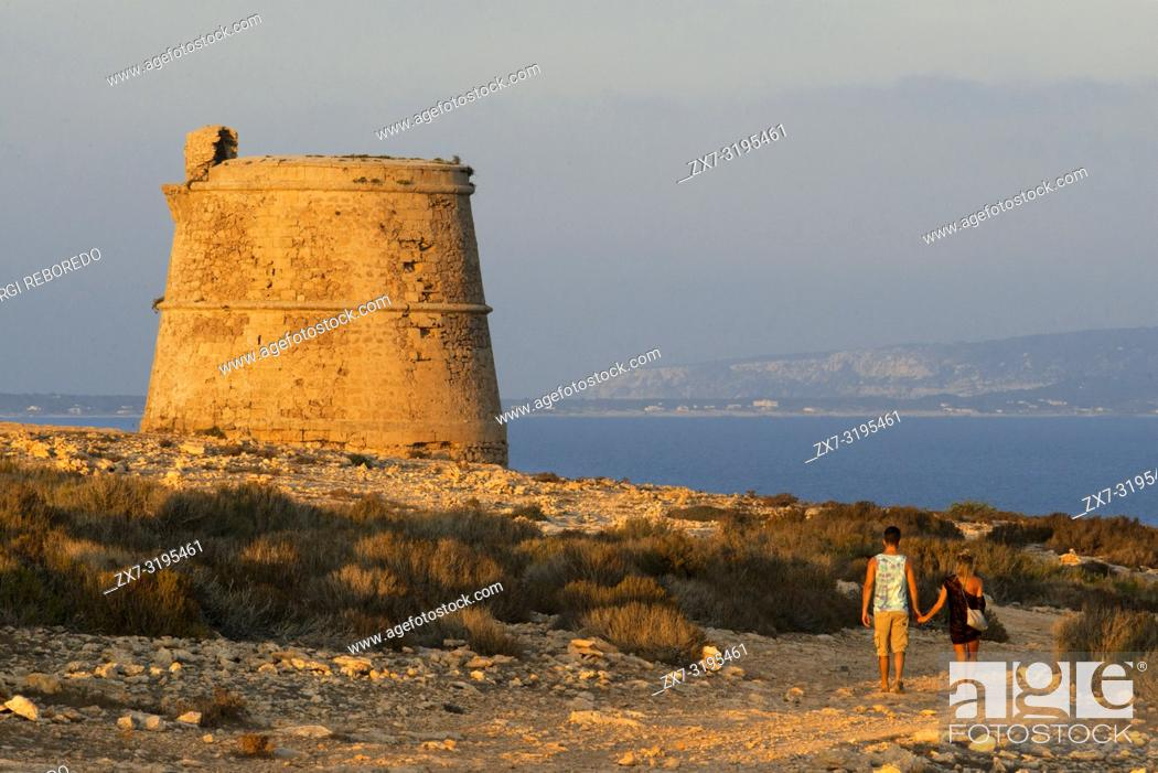 Stock Photo: Garroveret Tower on suntet. A couple of tourist taken pictures in Torre des Garroveret - one of the towers on Formentera, Balearic Islands, Spain.