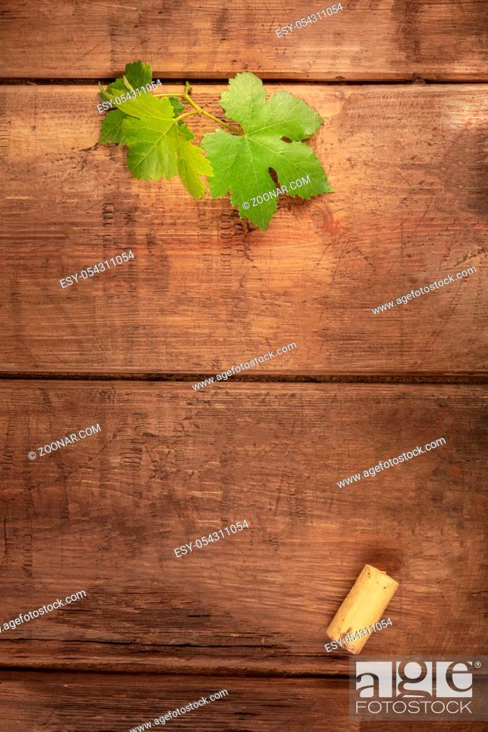 Stock Photo: A vine leaf and a wine cork, shot from the top on a dark rustic background with a place for text.