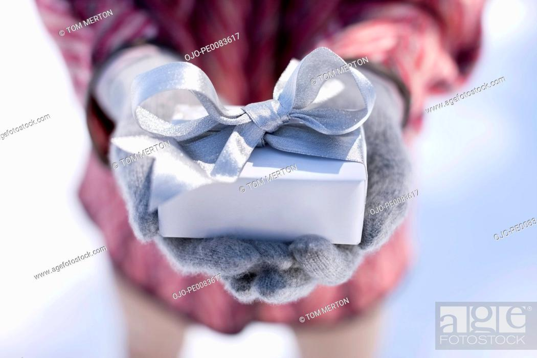 Stock Photo: Close up of hands cupping Christmas gift with silver ribbon.