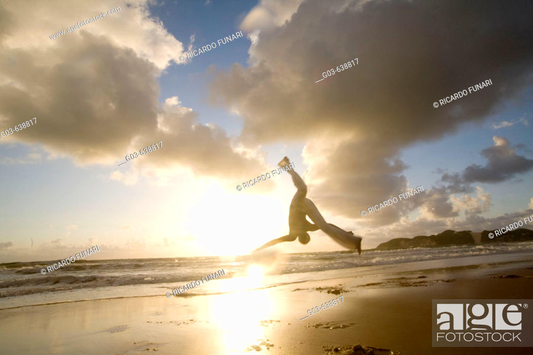 Stock Photo: Capoeira player training and exercising in the beach, Brazil.