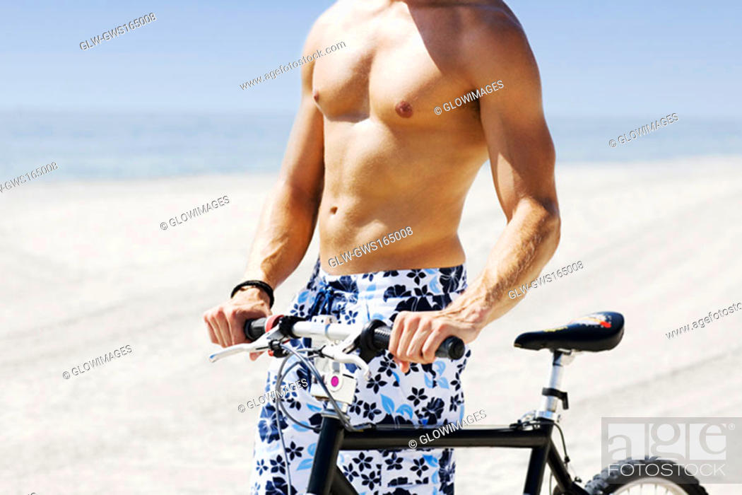 Stock Photo: Mid section view of a man with a bicycle on the beach.