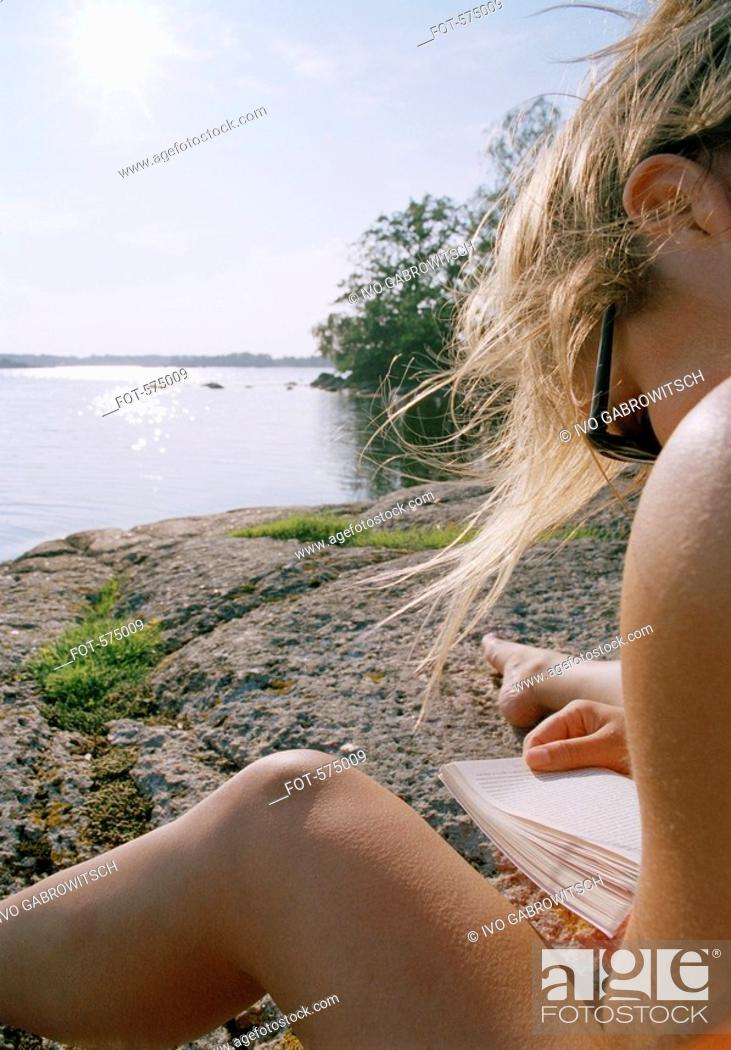 Stock Photo: A young woman reading by a lake.