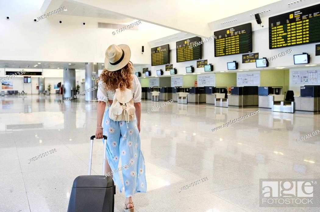 Stock Photo: Young woman with baggage at the airport departure hall.