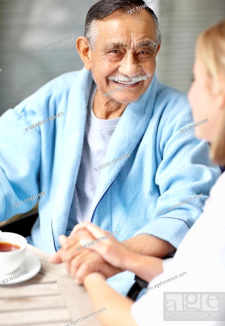 Stock Photo: Nurse and senior patient sitting at table.