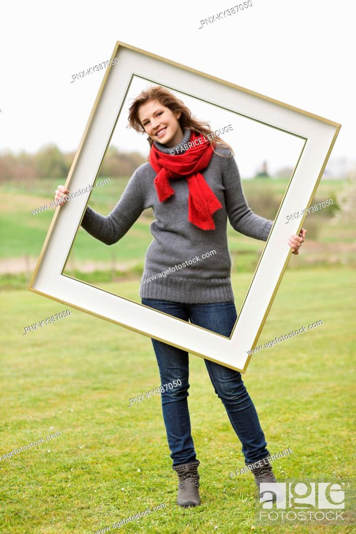 Stock Photo: Portrait of a woman standing with a frame in a park.