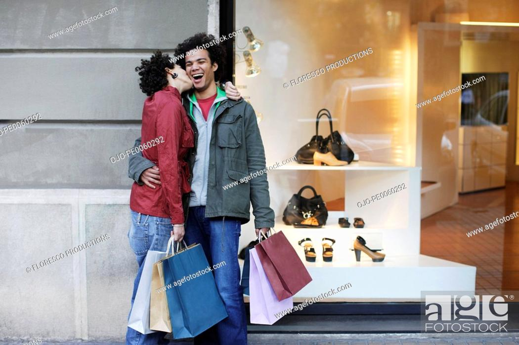Stock Photo: Couple outdoors with shopping bags kissing.