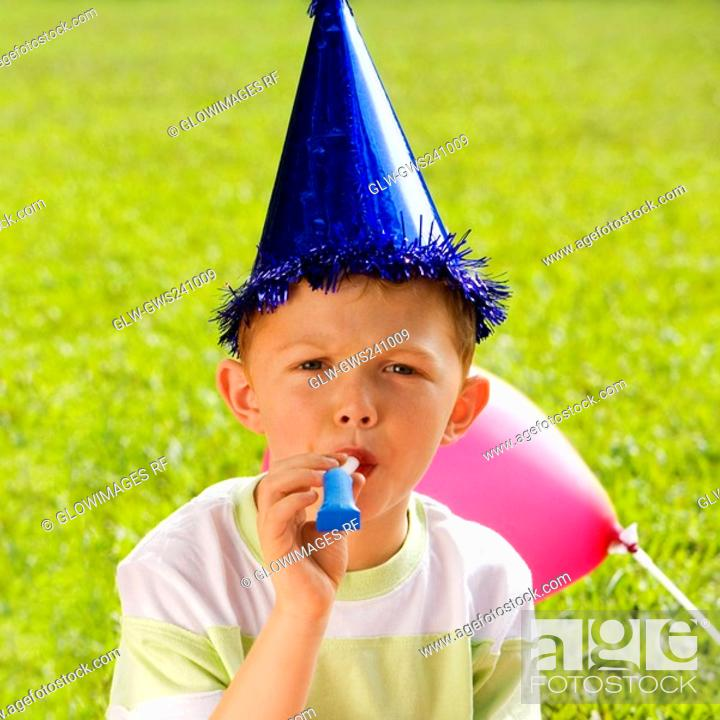 Stock Photo: Portrait of a boy blowing a party horn blower.