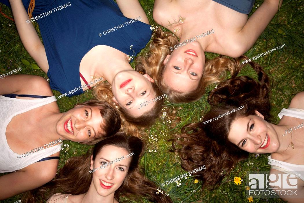 Stock Photo: Five cheerful female friends lying in the grass, head and shoulders.