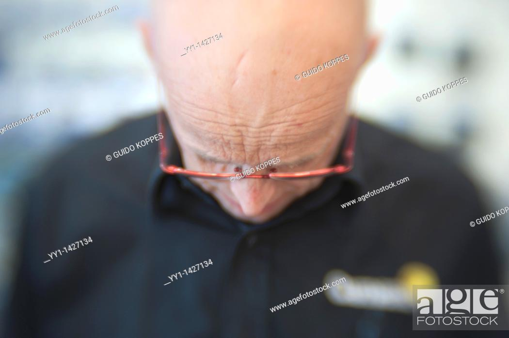 Stock Photo: Rotterdam, Netherlands. Bald man wearing glasses working in a store serving a customer.