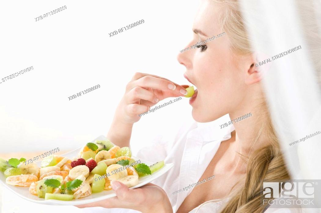 Stock Photo: Woman eating fruit salad.