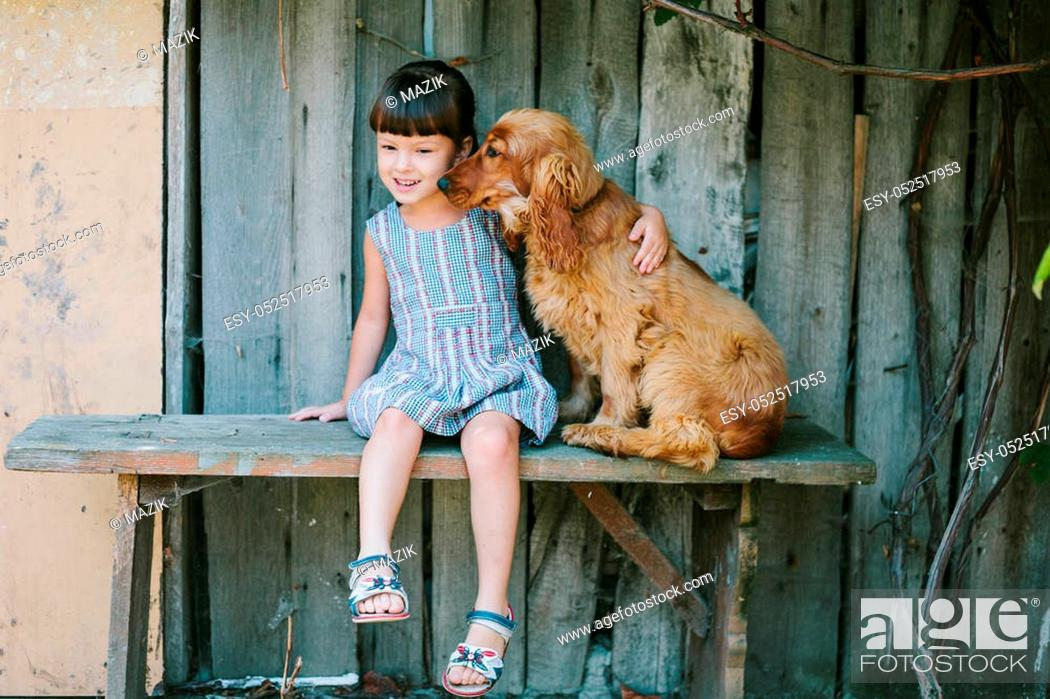 Stock Photo: country girl sitting on a bench with her dog under vine. girl playing with her dog. wooden background.