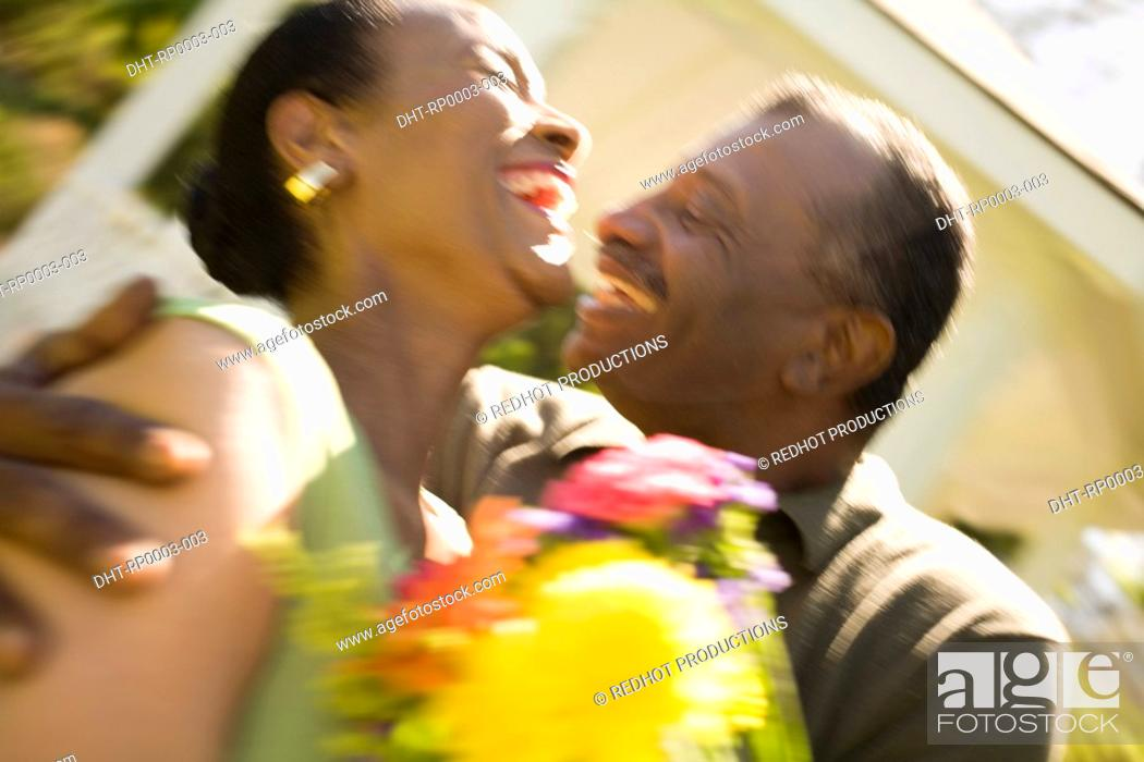 Stock Photo: A couple with flowers outdoors.