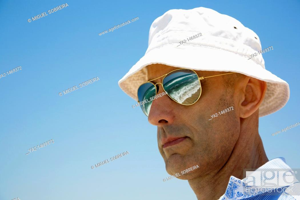 Stock Photo: Mature Male with sunglasses reflecting ocean.