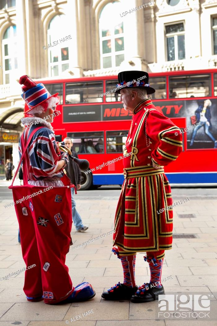Stock Photo: Two people in British themed costumes pose with a red bus in the background.