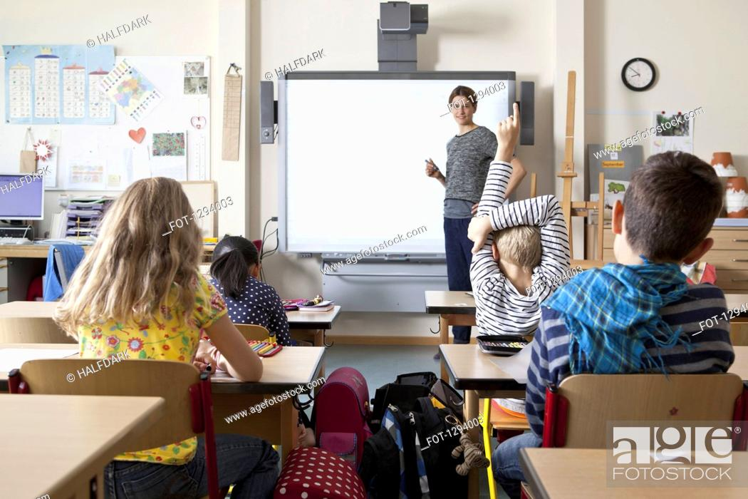 Stock Photo: Teacher teaching to students in classroom.
