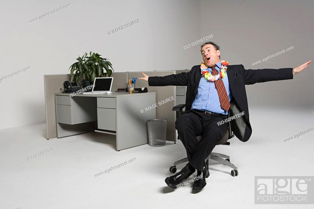 Stock Photo: Businessman messing around on office chair.