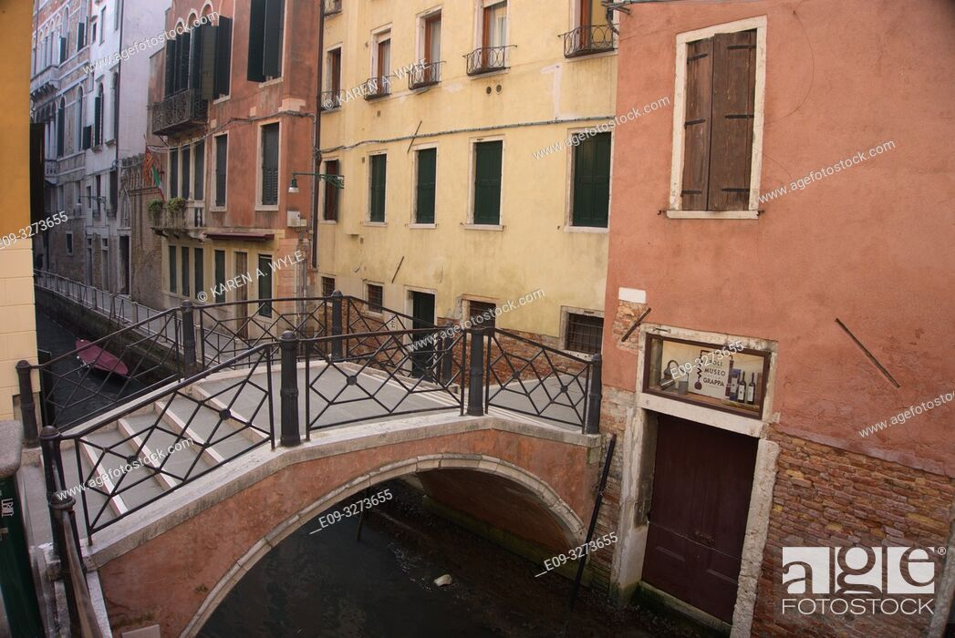 Stock Photo: short bridge over narrow canal, yellow and rust-red buildings, muted colors, Venice, Italy.