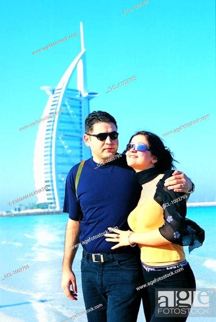 Stock Photo: Western tourist couple on the beach near Burj Al Arab hotel in Dubai, UAE.