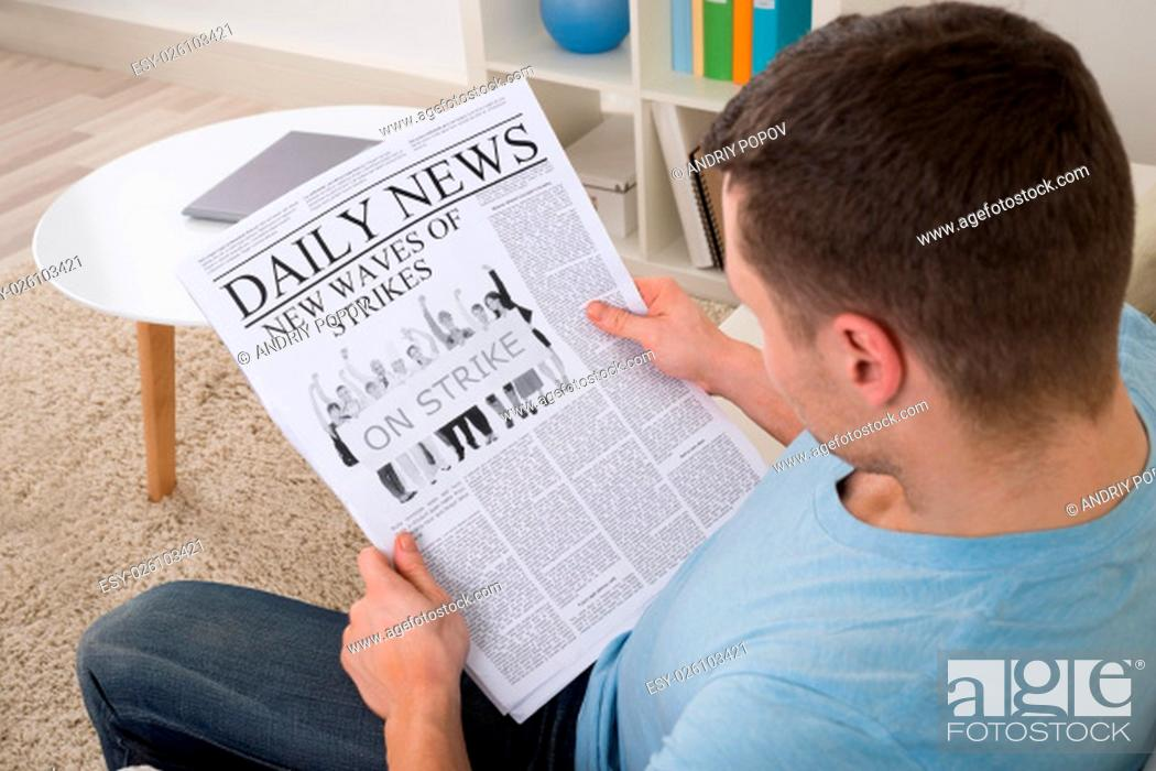 Stock Photo: High angle view of mid adult man reading news on newspaper at home.