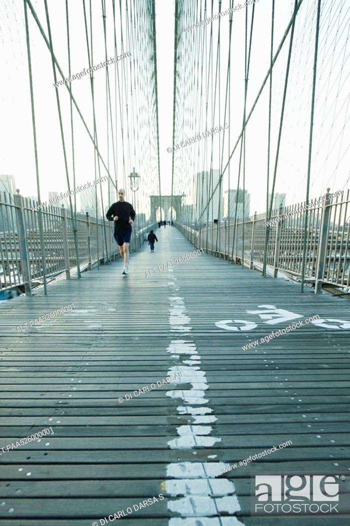 Stock Photo: Jogger running across pedestrian walkway of Brooklyn Bridge in New York City, Manhattan skyline in distance.