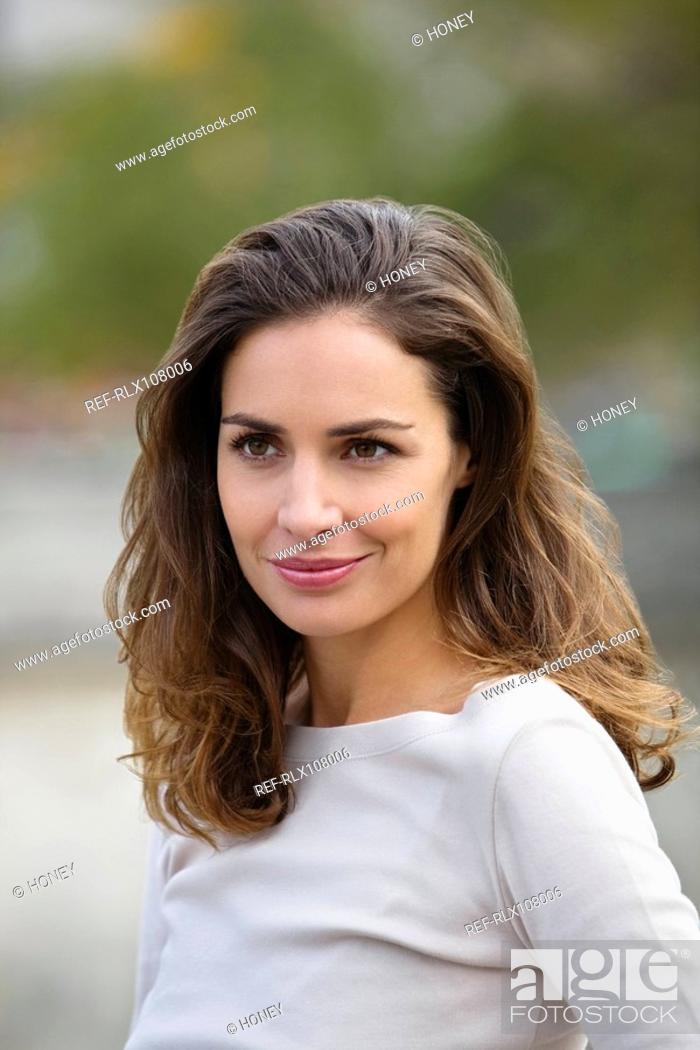 Stock Photo: Portrait of young woman smiling, Paris, France.
