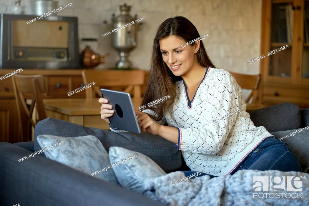 Stock Photo: beautiful young smiling woman in white sweater sitting with a tablet on a gray sofa.