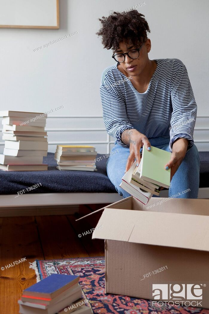 Stock Photo: Young woman packing books in cardboard box at home.