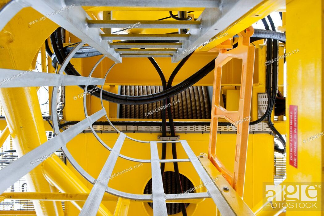 Stock Photo: Safety railing around the steps, leading to the hydraulic tubing and steel cables of a huge industrial winch. Detail of a crane.