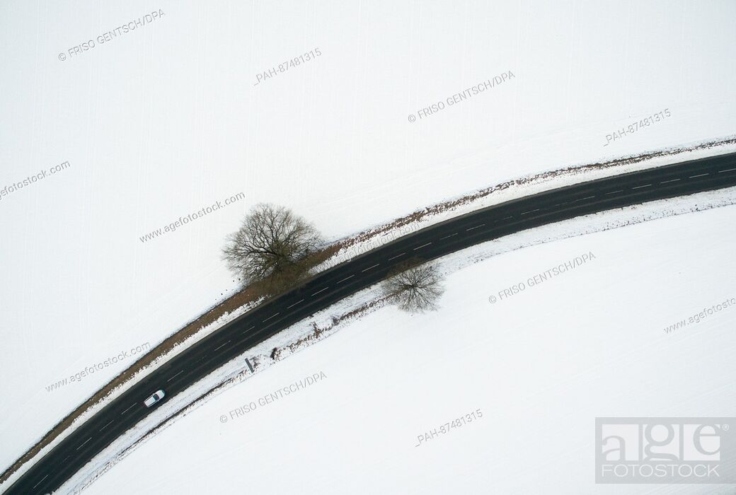 Stock Photo: A car drives down a street which is surrounded by snowy grounds near Bad Driburg, Germany, 24 January 2017. Aerial view taken with a drone.