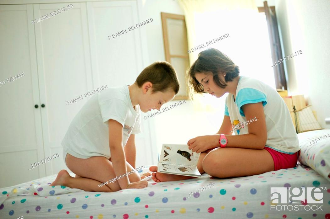 Stock Photo: boy and girl on a bedroom reading a book, Ludiente, Castellón, Spain.