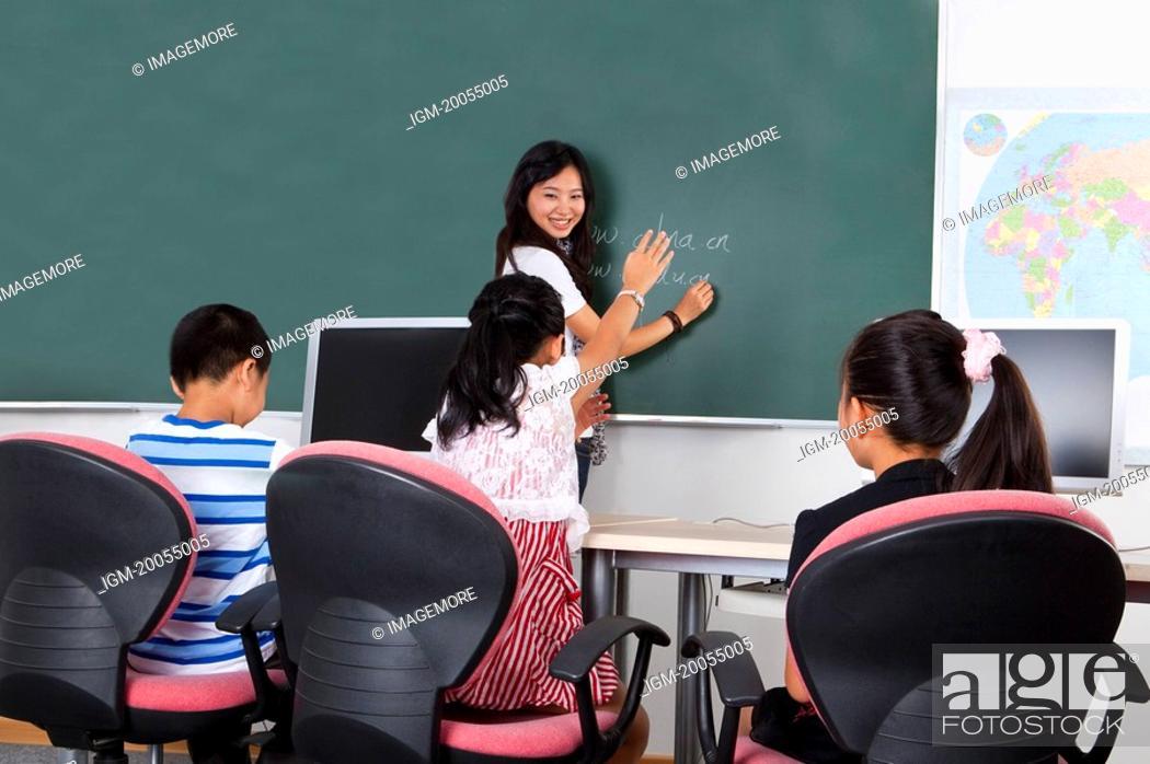 Stock Photo: Child, Young teacher teaching three children and smiling.