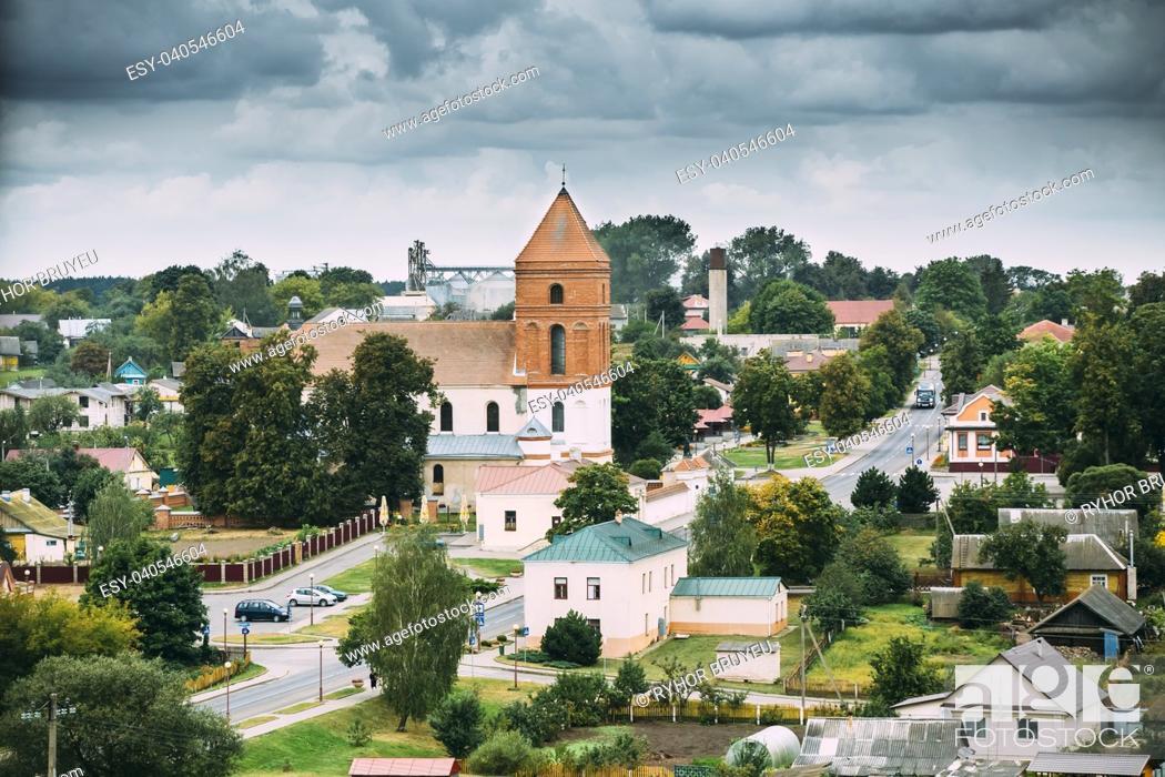 Stock Photo: Mir, Belarus. Landscape Of Village Houses And Saint Nicolas Roman Catholic Church In Mir, Belarus. Famous Landmark.