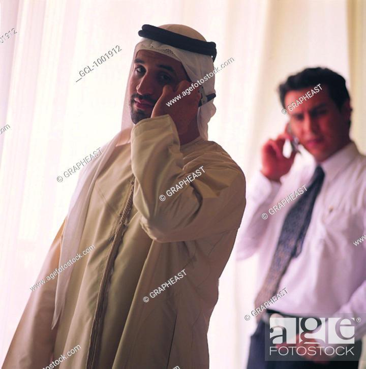 Stock Photo: Arab businessmen using mobile phones.