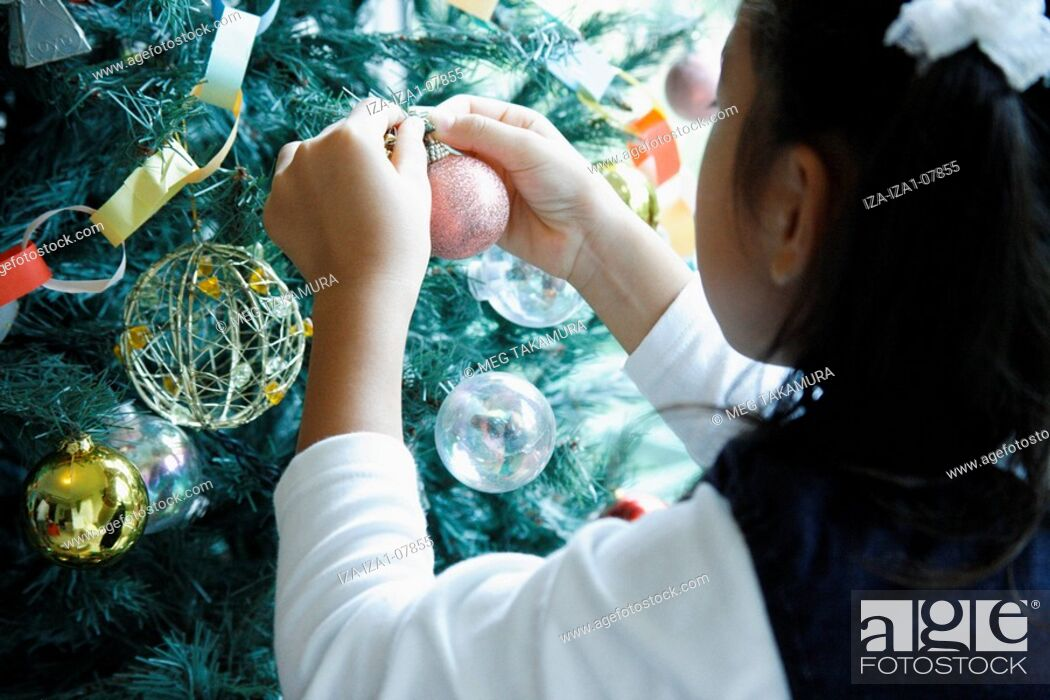 Imagen: Rear view of a girl decorating a Christmas tree.
