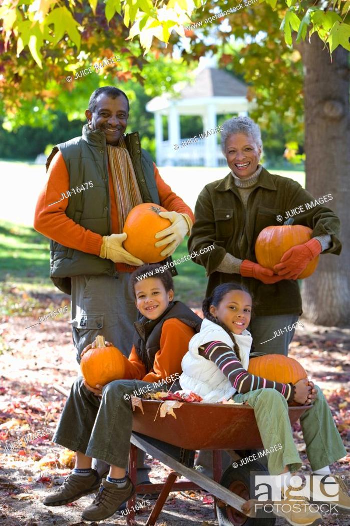 Stock Photo: Grandparents and grandchildren holding pumpkins in autumn.