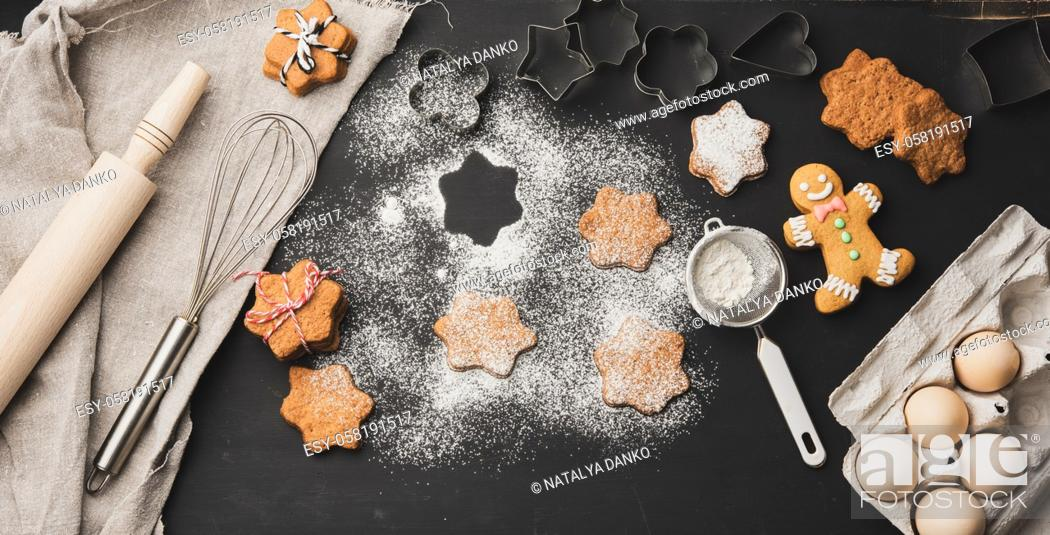 Stock Photo: Star shaped baked gingerbread cookies sprinkled with powdered sugar on a black table, top view.