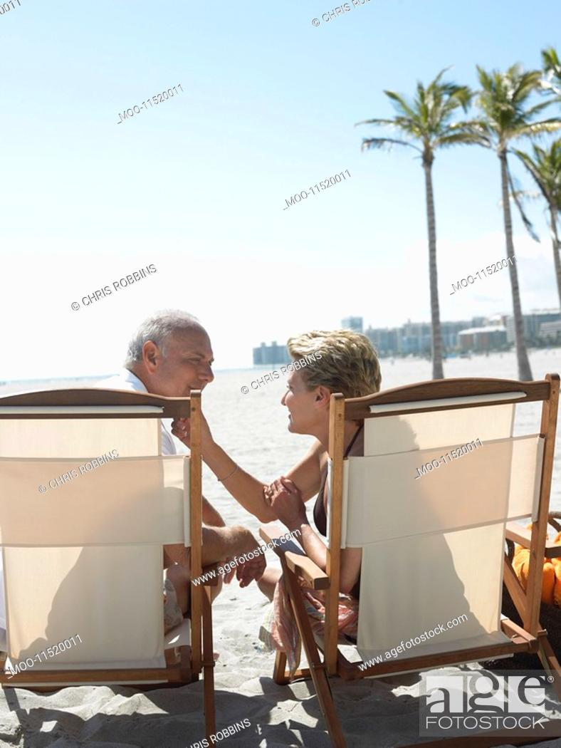 Stock Photo: Senior couple on sunloungers on tropical beach back view.