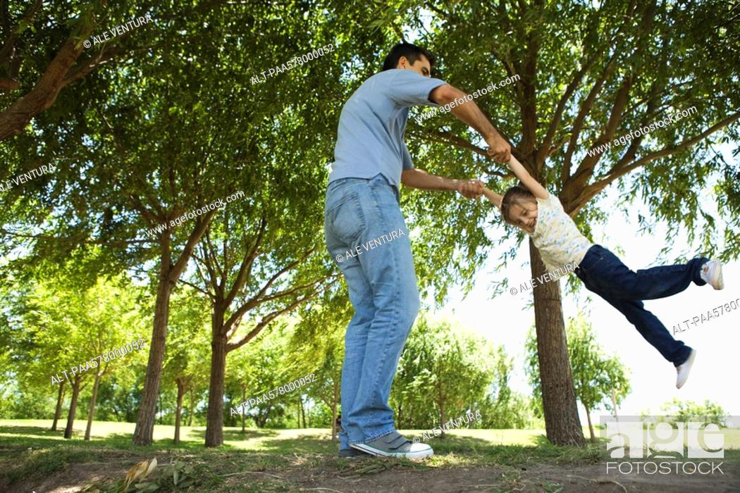 Stock Photo: Father swinging his young daughter by her arms.