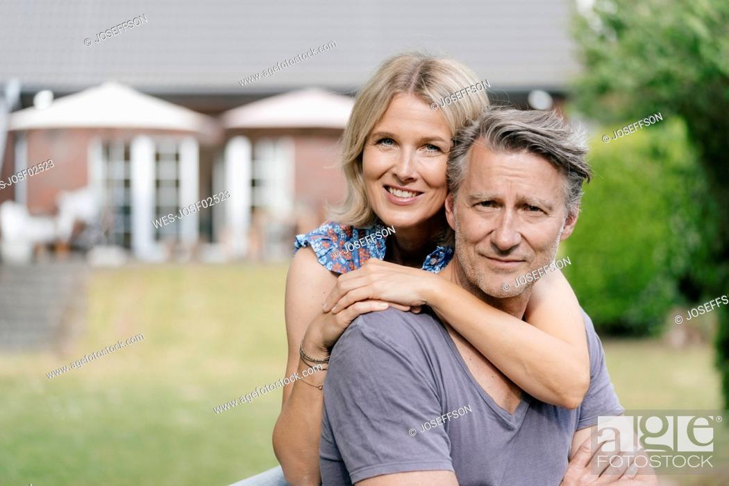 Stock Photo: Portrait of smiling mature couple embracing in garden of their home.