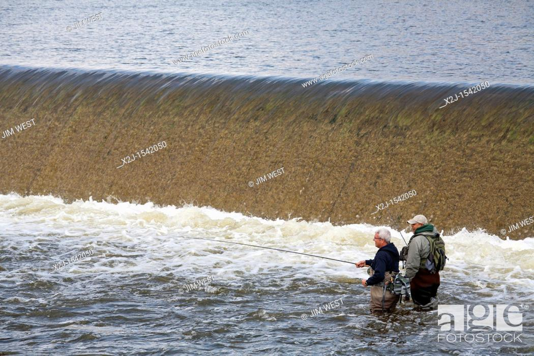 Stock Photo: Grand Rapids, Michigan - Fishermen below a dam on the Grand River in downtown Grand Rapids.
