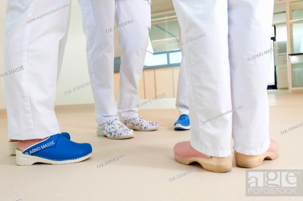 Stock Photo: Low section of group of nurses wearing surgical scrubs and clogs.